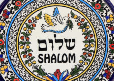 decorative plate with the image of a dove carrying an olive branch and inscription peace in Hebrew and English